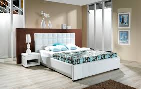 white wooden single bed with white fabric headboard and blue