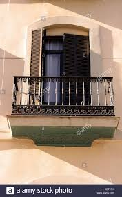 spanish window with wrought iron balcony and wooden shutters stock
