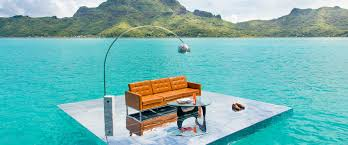 gray malin floats midcentury furniture in turquoise water