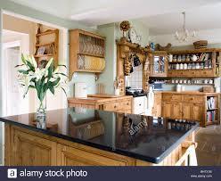 vase of white lilies on black granite worktop on island unit in