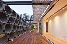 screens made out of raw concrete pipes provide privacy for this