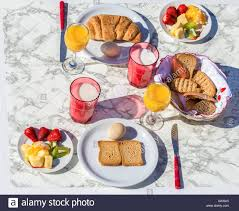 set table with various food and drink for breakfast on sunny day