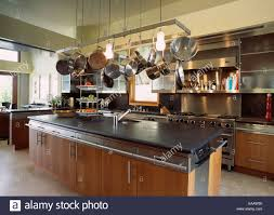 kitchen cupboard storage pans pans on metal storage rack above island unit with wooden