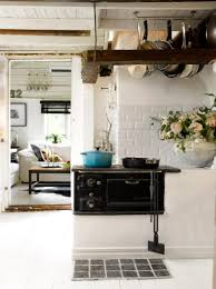 cottage kitchen evoking warm ambience and traditional wooden suspended cooker hooks and subway backsplash tile in beautiful cottage kitchen feat white wood ceiling