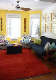 a large red rug and blue couch and ottoman are pulled together by