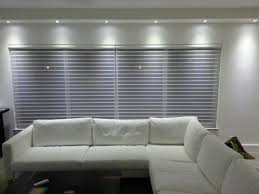 window basement design with white sectional sofa and 3 day blinds