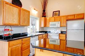 white kitchen countertops with brown cabinets light brown cabinets with black counter tops white kitchen appliances