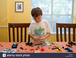 7 year old mexican american boy plays builds and looks at box to