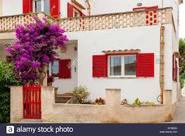 wonderful white two story house with red wooden shutters and gates