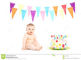 baby birthday baby boy sitting next to a birthday cake and party flags