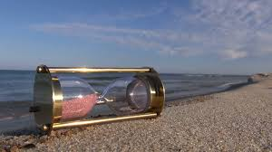 hourglass sandglass with pink sand on the beach by the sea on