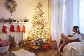 Christmas Decoration In Home Child Sitting Near Decorated Christmas Tree And Fireplace