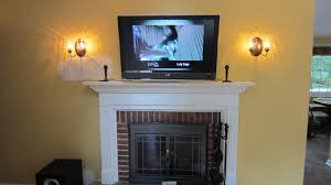 mounting tv above black and red brick fireplace with white mantel