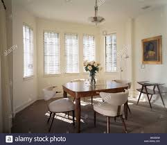 fifties white leather chairs and forties table in modern stock fifties white leather chairs and forties table in modern fifties style american dining room with brown carpet
