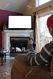 bored man watches a big screen flat panel tv in his living room