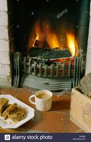 cup of tea and cake by open real log fire in living room by