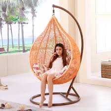 orange hanging chair with brown iron holder fits the white outdoor