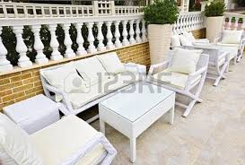 patio with white wicker furniture with view of mediterranean