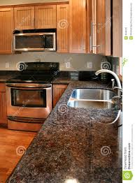kitchen wood cabinets black and stainless stove royalty free stock