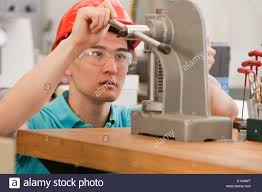 engineering student operating a manual bench top c frame press