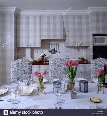 pink tulips on dining table in kitchen with blue floral