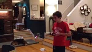 kid lands ornament on christmas tree with remote control