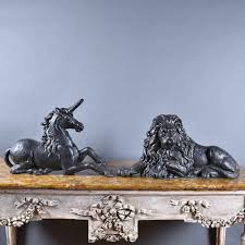 pair of cast iron lion and unicorn andirons boot scrapers