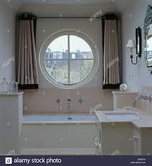 beige silk curtains on either side of circular window above bath