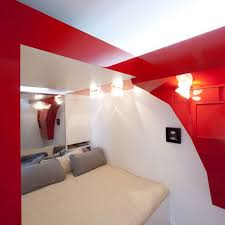 comfortable small bedroom with red white color and beige bed cover