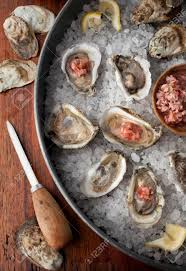 mignonette cuisine oysters in shells on a bed of salt with lemon wedges and a