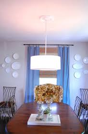 dining room with drum pendant lighting and simple medallion