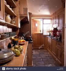 stone floor tiles in narrow country kitchen with fitted wooden