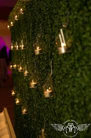 hanging votives on a hedge wall creates a soft lighting detail in