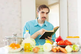 livre cuisine homme homme bel faisant cuire des légumes avec le livre de cuisine photo