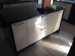 high gloss cream magnet kitchen with black granite surround