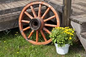an old wagon wheel used as an outside decoration for a home deck