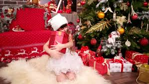 child enjoys gifts for christmas little plays with gifts in