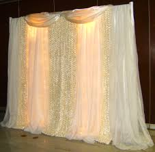 wedding backdrop tulle curtain lights and sheer fabric would make a neat backdrop for a