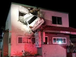 two storey building car goes airborne gets wedged in upper wall of two storey