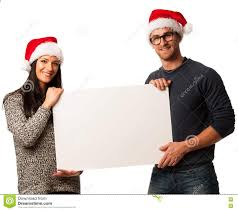 young couple in santa hats holding blank board for advertisement