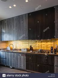 gold leaf backsplash in kitchen with dark smoky oak cabinetry