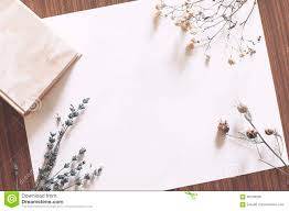 Drying Flowers In Books - blank paper on table with book and dried flowers stock photo