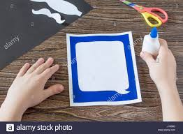 the child glues together the paper parts greeting card for