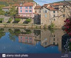 river aveyron with different houses colour pink with reflection at