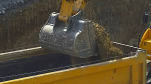 excavator loading soil on a dump truck slow motion close up video