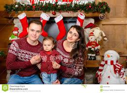 happy family beside the fireplace at christmas stock photo image