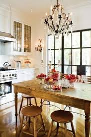 rustic wooden dining table with red fruit on table and chandelier