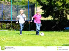 two brothers playing soccer in the garden stock photo image