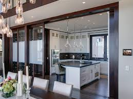 a sleek open kitchen is connected to the dining room via sliding