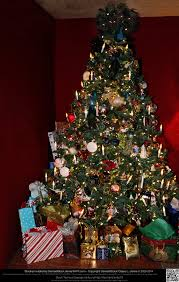 elaborately decorated christmas tree with gifts by damselstock on